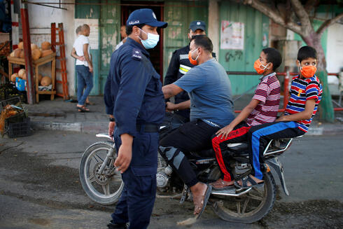 A Palestinian man with his children wearing protective face masks rides his motorcycle by police officers amid the coronavirus disease (COVID-19) outbreak, in the northern Gaza Strip