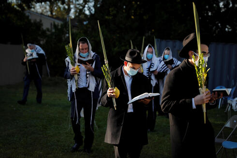 """Orthodox Jews gather for """"Hoshanot prayers"""" as part of their Sukkot observance on a neighborhood lawn to avoid over-crowding at an indoor synagogue, following the outbreak of the coronavirus disease (COVID-19) in the New York City suburb of Monsey"""