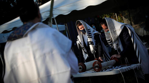"""Men read from the Torah as Orthodox Jews gather for """"Hoshanot prayers"""" as part of their Sukkot observance on a neighborhood lawn to avoid over-crowding at an indoor synagogue, following the outbreak of the coronavirus disease (COVID-19) in the New York City suburb of Monsey"""