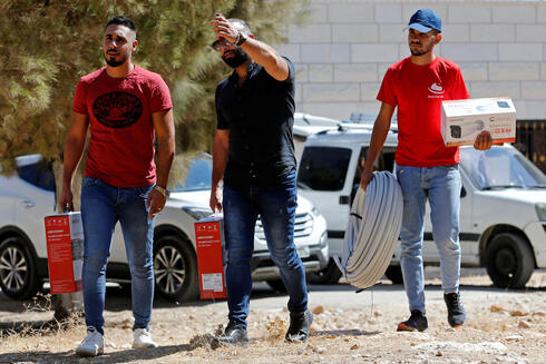 Workers arrive to install a video surveillance system to keep an eye on nearby Israeli settlers who Palestinians accuse of frequent attacks, in the village of Kisan in the Israeli-occupied West Bank