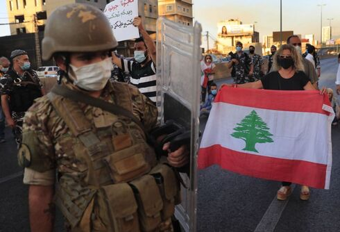 A Lebanese army soldier passes in front of an anti-government protester holding a national flag and blocking a main highway that links Beirut with north Lebanon during a protest against rising prices and worsening economic and financial conditions