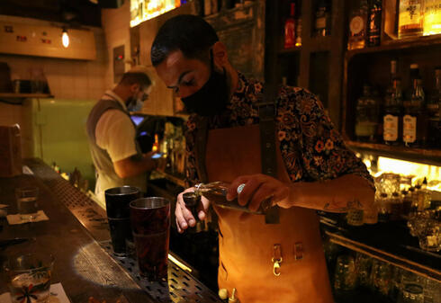 A bartender wearing a protective face mask prepares an alcoholic drink at a bar, amid concerns over the spread of the coronavirus disease (COVID-19), in Beirut, Lebanon