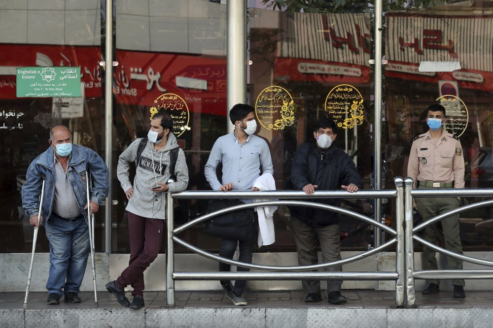 People wear protective face masks to help prevent the spread of the coronavirus in downtown Tehran