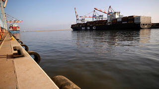 An MSC cargo ship, carrying containers, including some from the United Arab Emirates, docks as its cargo is unloaded at Haifa's port,