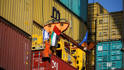 Containers carrying goods from the United Arab Emirates, which entered Israel on an MSC cargo ship, are unloaded with a cargo crane bearing Israeli and Emirati flags at Haifa's port