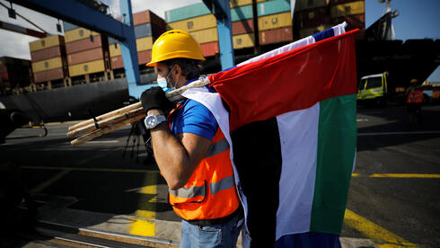 A worker carries Israeli and Emirati flags, after containers carrying goods from the United Arab Emirates, which entered Israel on an MSC cargo ship, were unloaded at Haifa's port