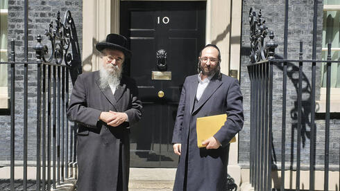 Rabbi Avrohom Pinter, left, stands beside Joel Friedman, right, the director of Public Affairs for the Interlink Foundation, an umbrella organization for Orthodox Jewish charities on July 4, 2019 in Downing Street, London
