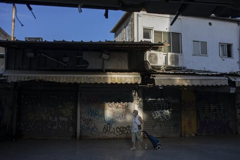 A woman wearing face mask as a precautionary measure against the coronavirus walks past closed shops in Tel Aviv