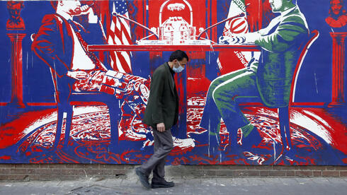 An Iranian man walk past an anti-US wall painting on the wall of former US embassy in Tehran, Iran