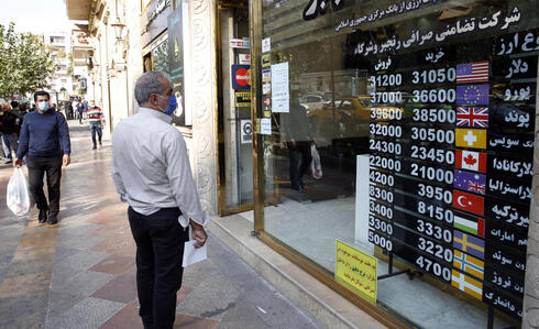 n Iranian man checks the currency rate as he walks past a currency exchange service in Tehran, Iran,