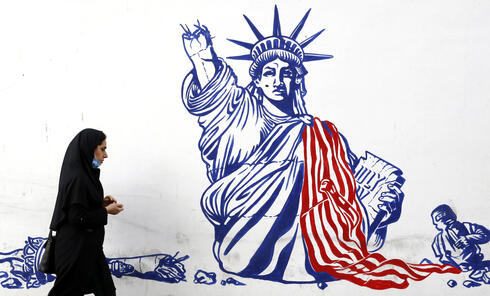 An Iranian woman walk past a mural depicting a defaced Statue of Liberty on the wall of former US embassy in Tehran, Iran