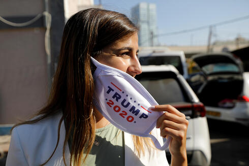 Activists from Republicans Overseas Israel, paste a pro-Trump election campaign ad on a minibus in Tel Aviv, Israel October 14, 2020