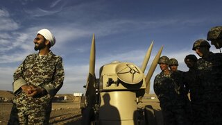 an Iranian clergyman stands next to missiles and army troops, during a manoeuvre, in an undisclosed location in Iran