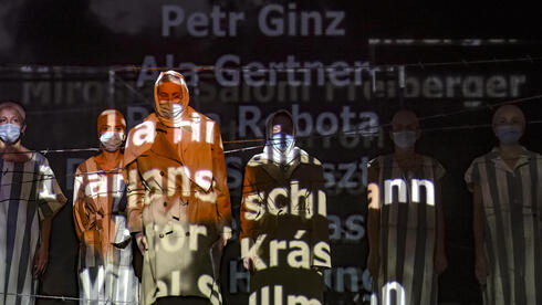"""Names of victims scroll on a mesh at the Jewish State Theatre as actresses perform wearing face masks for protection against COVID-19 infection, during the rehearsals for premiere of the """"The Beautiful Days of My Youth"""""""