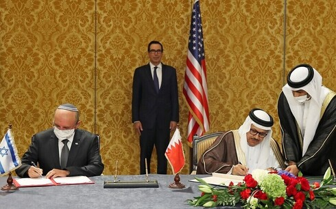 The head of the Israeli delegation, National Security adviser Meir Ben Shabbat (L), and Bahraini Foreign Minister Abdullatif bin Rashid Al-Zayani, sign the Israel-Bahrain accord formalizing diplomatic relations, in the Bahraini capital Manama, on October 18, 2020. US Treasury Secretary Steve Mnuchin (C) looks on