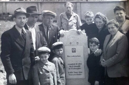 The Eisenberg and Brandspiegel families gather around the tombstone of Abraham Eisenberg at the Hallein Displaced Persons Camp in Austria in June 1948