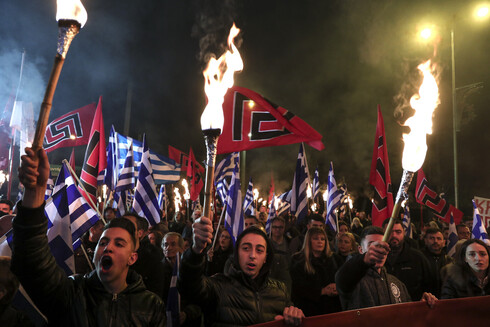 Supporters of Greece's extreme right Golden Dawn raise torches during a rally in Athens