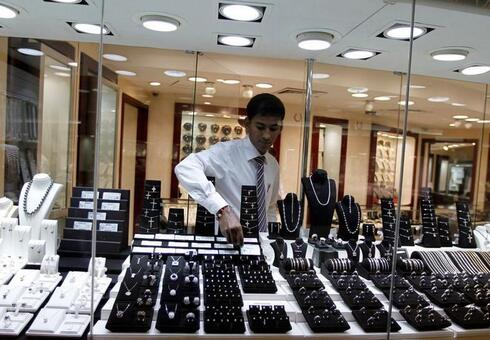 A staff member at a jewelry store places a diamond in the window display at Dubai's Gold and Diamond Park