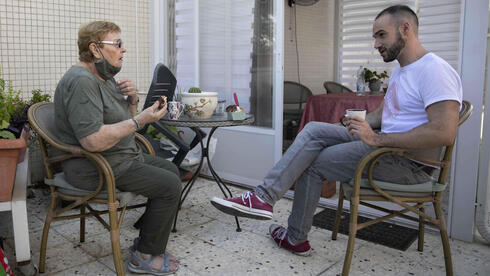 Israeli volunteer Sharon Yaron, left, brings a cake to 85-year-old Holocaust survivor Sara Weinsten during a visit to her house in Yavne, Israel, Thursday, Oct. 8, 2020