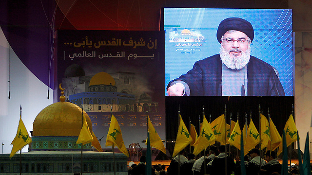 Hezbollah members watch as the terror group's leader Hassan Nasrallah delivers an address via video