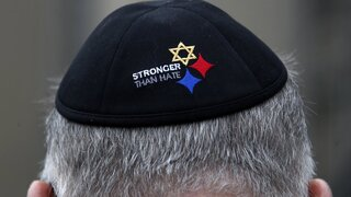 """a man wearing a """"Stronger Than Hate"""" yarmulke stands outside the Tree of Life synagogue in Pittsburgh on the first anniversary of the shooting at the synagogue,"""