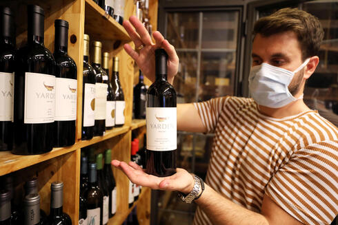 shop owner holds a bottle of wine from the Golan Heights Winery