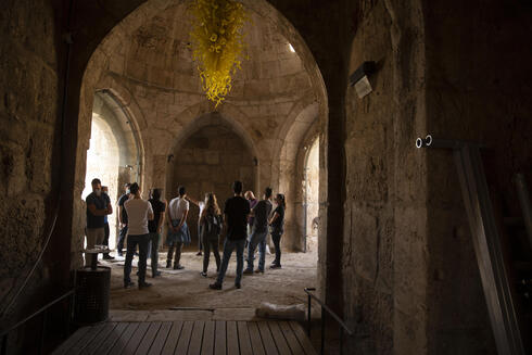 A group gathers under a work by American sculptor Dale Chihuly at the Tower of David Museum in the Old City of Jerusalem, Oct. 28, 2020