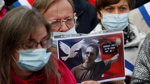 A person holds a picture of Samuel Paty, the French teacher who was beheaded on the streets of the Paris suburb of Conflans St Honorine