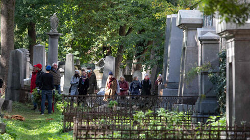 A group of visitors take part in a tour at the old Waehring Jewish cemetery