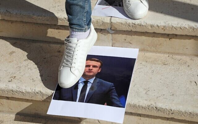 Stepping on the photograph of French President Emmanuel Macron in protest of his condemnation of Islamic extremism
