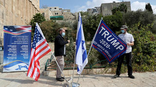 An Israeli settler adjusts a flag during a gathering to show support for U.S. President Donald Trump in the upcoming U.S. election, at the Cave of the Patriarchs, in the Palestinian city of Hebron