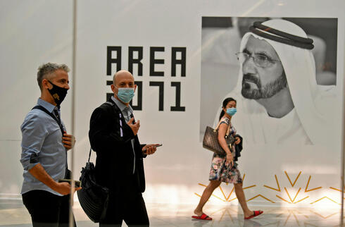 Members of Israeli high-tech delegation walk past a poster of Dubai's ruler Sheikh Mohammed bin Rashid al-Maktoum during a meeting with Emirati counterparts at the headquarters of the Government Accelerators in Dubai