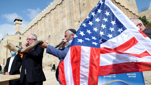 Israeli settlers blow the Shofar, a ceremonial ram's horn, as they gather to show their support for U.S. President Donald Trump in the upcoming U.S. election,