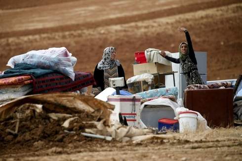 Palestinian Bedouins with their scattered belongings after Israeli soldiers demolished their tents in an area east of the village of Tubas in the occupied West Bank