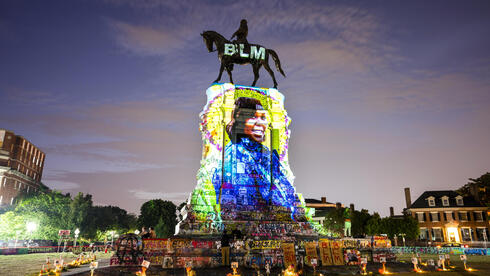 A photograph of Breonna Taylor, who was killed in her own apartment by Louisville police officers, is projected onto a statue of Confederate General Robert E. Lee