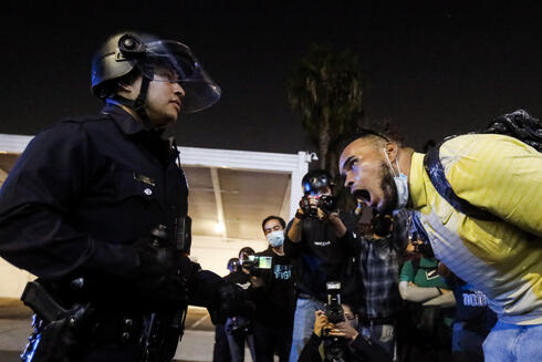 A man yells at a police officer during a protest on Election Day,