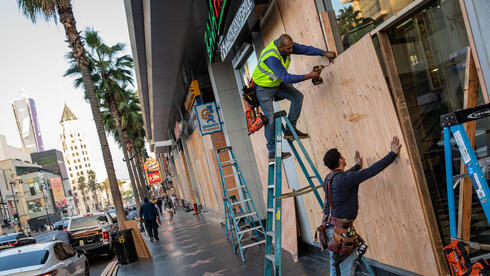 Workers from BluSky, an emergency services and restoration company, secure plywood to protect windows along Hollywood Boulevard on election day.