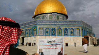 """A Palestinian man reads the front page of Al-Quds newspaper, headlined in Arabic """"Joe Biden the new US President"""" in front of the Dome of the Rock in the al-Aqsa mosque compound"""