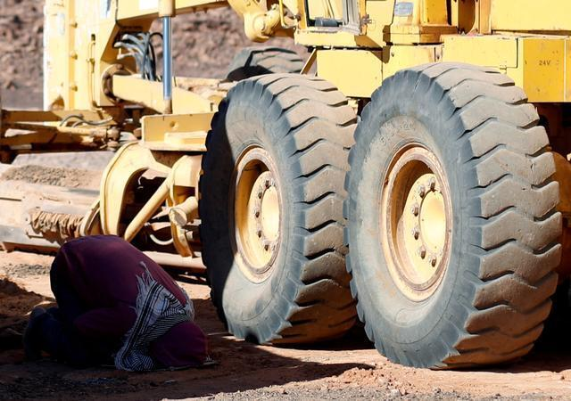 A woman praying in the shadow of bulldozers in northern Sinai
