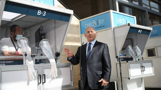 Prime Minister Benjamin Netanyahu stands next to a Check2Fly coronavirus testing booth at Ben Gurion Airport, November 2020