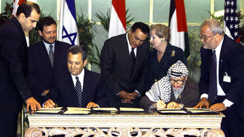 Saeb Erekat, right, watches as then-Prime Minister Ehud Barak and Palestinian leader Yasser Arafat sign an agreement paving the way for talks on a permanent peace settlement, Sept. 1999