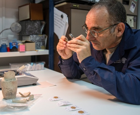 Dr. Robert Kool, IAA coin expert examines a gold coin discovered in an archeological dig in Jerusalem