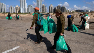 Israelis who lost their jobs due to Covid-19 coronavirus pandemic crisis, work on a new job collecting trash on the beach at the Peleg Nature reserve in the Mediterranean coastal city of Netanya