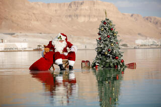 Issa Kassissieh, wearing a Santa Claus costume, looks on as he poses for a picture while sitting next to a Christmas tree on a salt formation in the Dead Sea