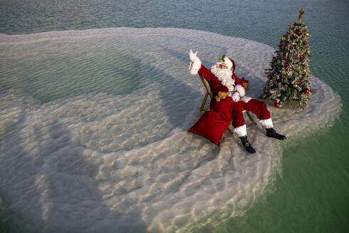 Issa Kassissieh, dressed as Santa Claus, waves next to a Christmas tree erected on a salt formation during filming for a Christmas greeting video from the Holy Land in the Dead Sea near Ein Bokeq, Israel