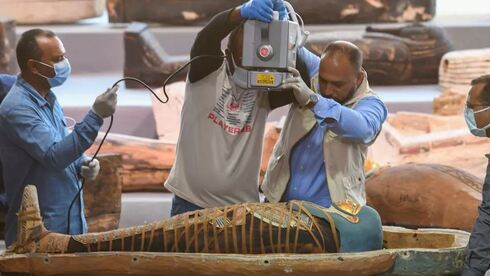 rchaeologists x-ray a mummy wrapped in a burial shroud and adorned with brightly coloured hieroglyphic pictorials, during the unveiling more than a 100 intact sarcophagi, at Egypt's Saqqara necropolis