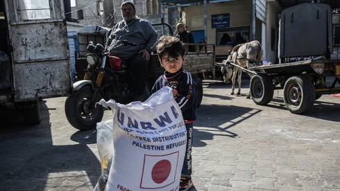 a child stands next to a sack of flour as people come to receive food aid from a United Nations Relief and Works Agency (UNRWA) distribution center in Khan Younis in the Gaza Strip