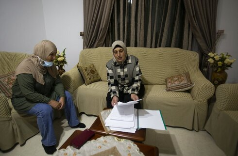 Palestinian sisters Kainat and Karema Quraan show documents of land ownership of land on which some of the Psagot vineyards and a winery building were established, at their home in the West Bank city of Al-Bireh