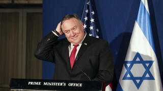 U.S. Secretary of State Mike Pompeo smiles while patting his head during a press conference with Israeli Prime Minister Benjamin Netanyahu