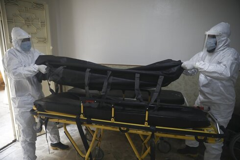 Civil defense personnel take the body of a person who died of corona virus from a hospital in Idlib, Syria